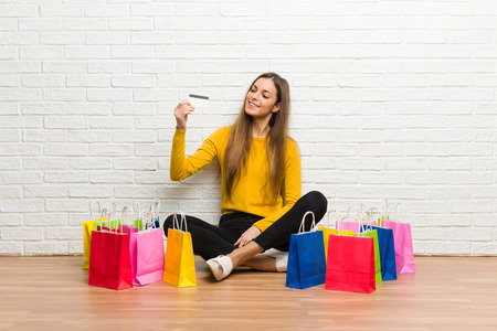 Young girl with lot of shopping bags holding a credit card and thinking