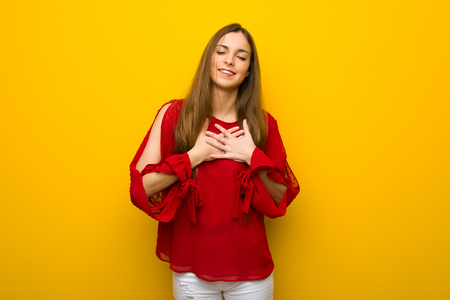 Young girl with red dress over yellow wall having a pain in the heart Stock Photo