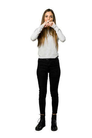 Full-length shot of young girl showing a sign of silence gesture on isolated white background