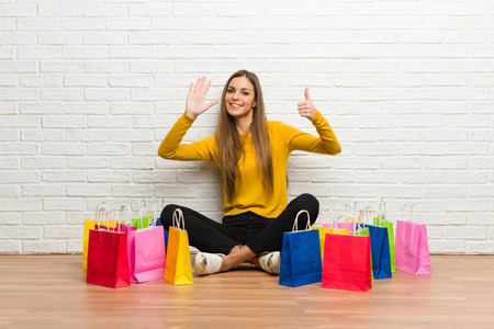 Young girl with lot of shopping bags counting six with fingers