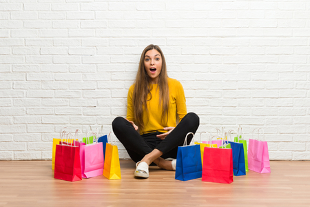 Young girl with lot of shopping bags with surprise and shocked facial expression