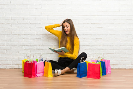 Young girl with lot of shopping bags surprised while enjoying reading a book