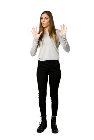 Full-length shot of young girl making stop gesture with both hands on isolated white background Stock Photo