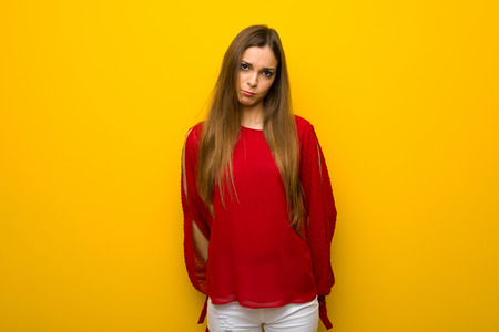 Young girl with red dress over yellow wall with sad and depressed expression