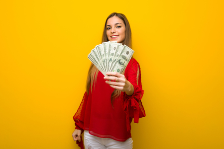 Young girl with red dress over yellow wall taking a lot of money Stock Photo
