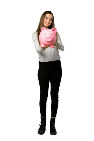Full-length shot of young girl holding a piggybank on isolated white background