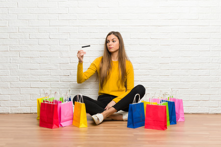 Young girl with lot of shopping bags taking a credit card without money Stock Photo