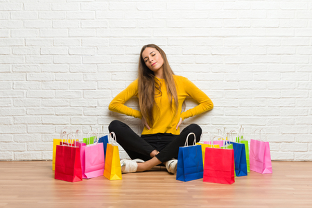 Young girl with lot of shopping bags suffering from backache for having made an effort