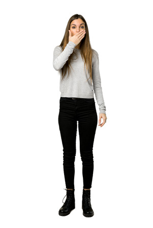 Full-length shot of young girl covering mouth with hands for saying something inappropriate on isolated white background