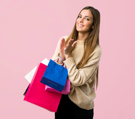 Young girl with shopping bags applauding after presentation in a conference on isolated pink background Stock Photo