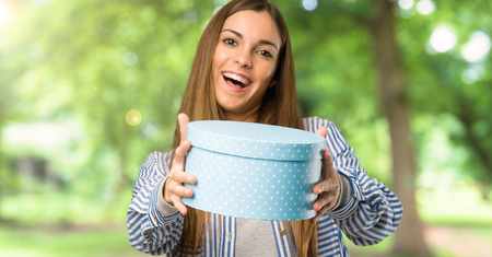 Young girl with striped shirt surprised because has been given a gift at outdoors Stock Photo