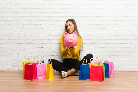 Young girl with lot of shopping bags holding a piggybank