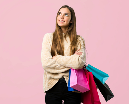 Young girl with shopping bags looking up while smiling on isolated pink background