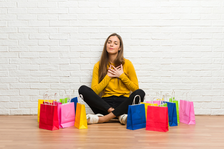 Young girl with lot of shopping bags having a pain in the heart Stock Photo