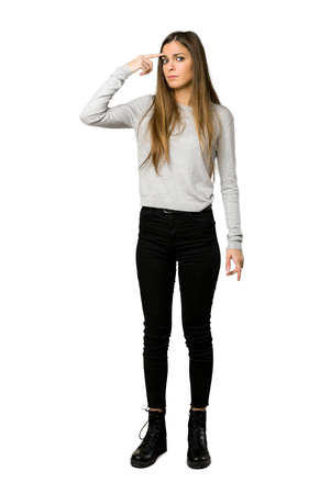 Full-length shot of young girl making the gesture of madness putting finger on the head on isolated white background