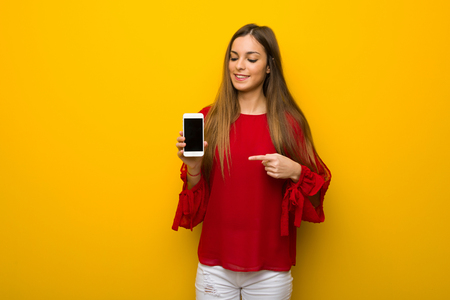 Young girl with red dress over yellow wall showing the mobile Stock Photo