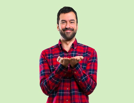 Handsome man holding copyspace imaginary on the palm on green background