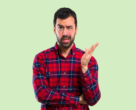 Handsome man unhappy and frustrated with something. Negative facial expression on green background