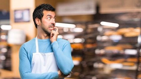 Man wearing an apron having doubts and with confuse face expression while looking up. Questioning an idea in a bakery Stock Photo