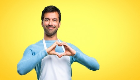 Man wearing an apron making heart symbol by hands. Being in love on yellow background