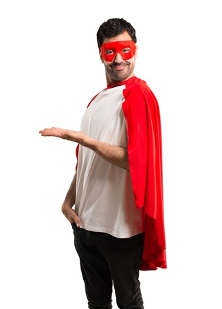 Superhero man with mask and red cape presenting a product or an idea while looking smiling towards on isolated white background
