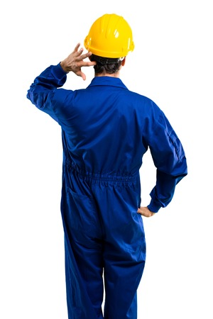Young workman with helmet on back position looking back while scratching head on isolated white background