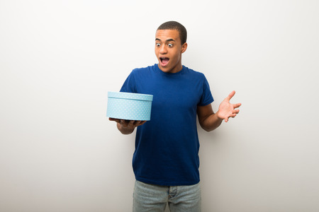 Young african american man on white wall holding gift box in hands