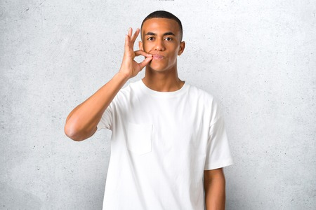 Young african american man showing a sign of closing mouth and silence gesture doing like closing his mouth with a zipper