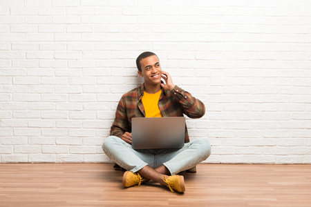 African american man sitting on the floor with his laptop thinking an idea while scratching head Stock Photo