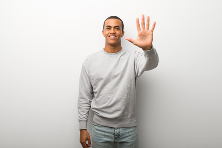 African american man on white wall background counting five with fingers