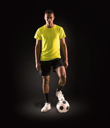 Uomo del giocatore di calcio con la riproduzione dalla pelle scura su sfondo scuro