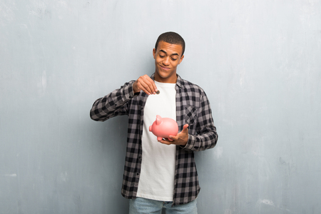 Young african american man with checkered shirt taking a piggy bank and happy because it is full
