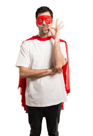 Superhero man with mask and red cape showing a sign of closing mouth and silence gesture doing like closing his mouth with a zipper on isolated white background Stock Photo