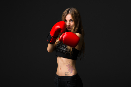 Sport woman with boxing gloves on dark background 写真素材