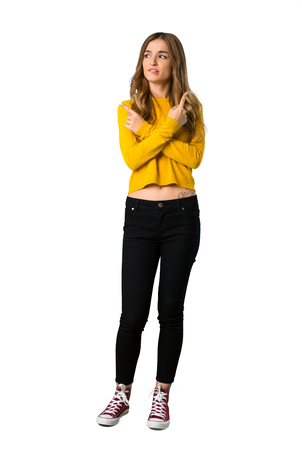 A full-length shot of a young girl with yellow sweater pointing to the laterals having doubts on isolated white background Standard-Bild
