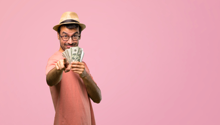 Man holding many bills points finger at you with a confident expression on pink background