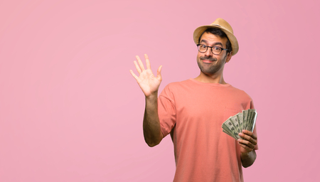 Man holding many bills saluting with hand with happy expression on pink background Фото со стока