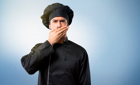 Chef man In black uniform covering mouth with hands for saying something inappropriate. Can not speak on blue background