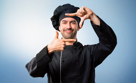 Chef man In black uniform focusing face. Framing symbol on blue background