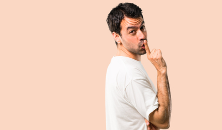 Young man with white shirt showing a sign of closing mouth and silence gesture putting finger in mouth on isolated ocher background