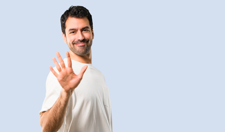 Young man with white shirt counting five with fingers on isolated blue background Stock Photo