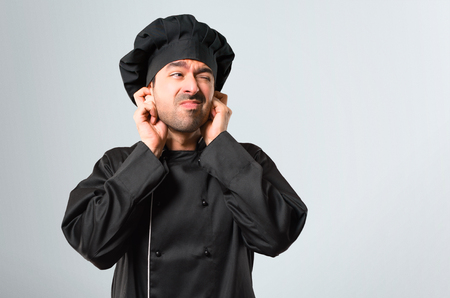 Chef man In black uniform covering both ears with hands. Frustrated expression on grey background