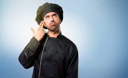 Chef man In black uniform with problems and with unhappy expression making gun gesture on blue background