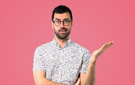 Handsome man with glasses unhappy and frustrated with something. Negative facial expression on pink background Reklamní fotografie