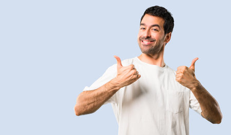 Young man with white shirt giving a thumbs up gesture and smiling because has had success on isolated blue background