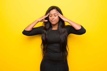 Young afro american woman on vibrant yellow background unhappy and frustrated with something