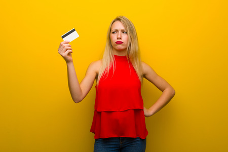 Young girl with red dress over yellow wall taking a credit card without money Archivio Fotografico