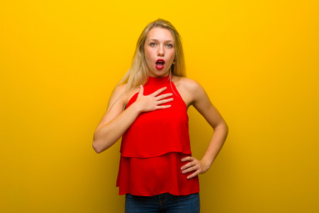 Young girl with red dress over yellow wall surprised and shocked while looking right