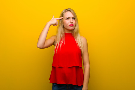 Young girl with red dress over yellow wall making the gesture of madness putting finger on the head