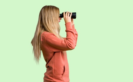 Young girl and looking in the distance with binoculars on green background Stok Fotoğraf